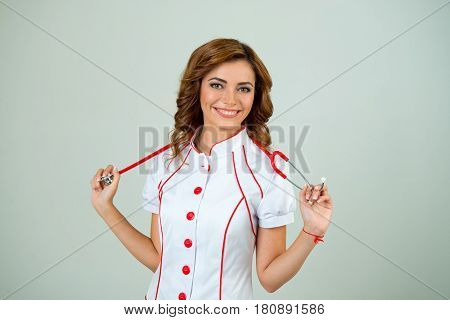 Portrait of young medical doctor woman smiling holding hands stethoscope and looking at camera. On white background.