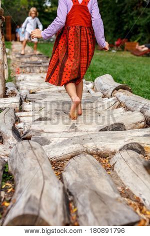 Little girl with barefoot and red dress walking on logs in a sensory garden
