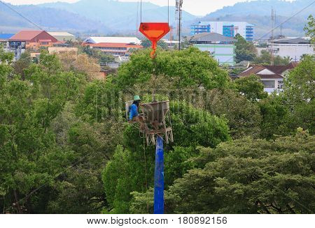 worker sit on concrete mixer and crane hook lifting container in construction site