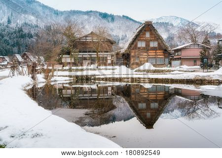 Old Style Traditional Houses With Reflection At Historic Village Shirakawago In Winter, Japan