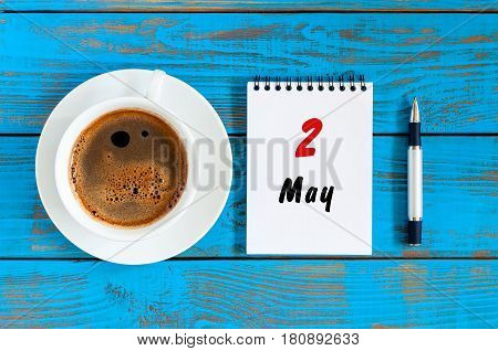 May 2nd. Day 2 of month, calendar written at notepad near morning coffee cup at blue wooden table, Top view. Spring time.