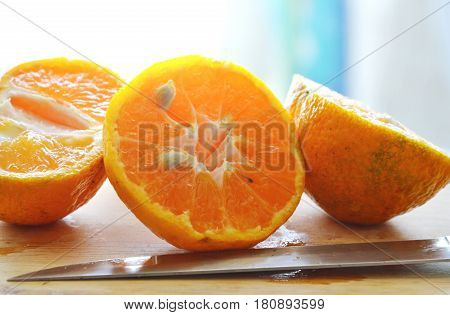 tangerine cut for squeeze on wooden chop block