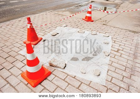 Plastic red cones warn pedestrians about repair of the sidewalk and sewerage hatchway. Moscow Russia.