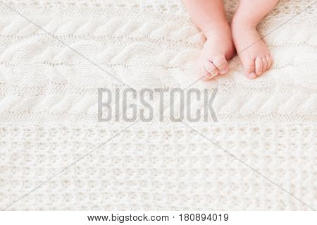Baby's feet on white knitted background. Little child's bare feet. Cozy morning bedtime at home. Place for text.