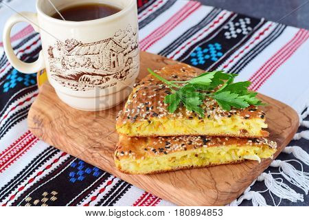 Two pieces of white cabbage pie with carrot on a black plate with cup of tea and the rest of the pie on a textile background. Healthy breakfast. Simple backing. Healthy eating concept