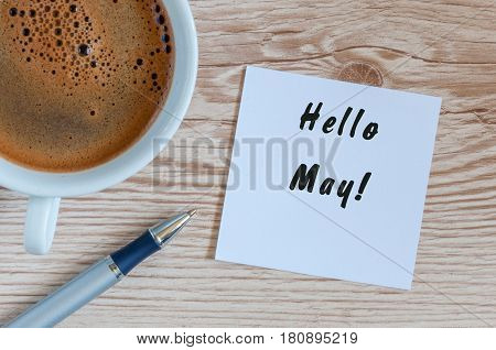 Hello May - message on wooden texture background with morning coffee mug. International Labor day Holiday concept.