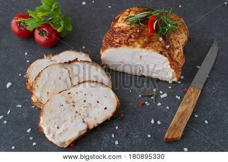 Roasted chicken breast for sandwiches with two cut pieces on a greay abstract background. Healthy eating concept