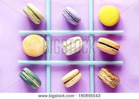 Various colorful french macaroons and straws on color background. Top view. Tic tac toe