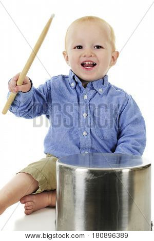 An adorable toddler sitting with and upraised drumstick, ready to play the crock pot before him.