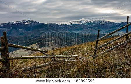 wooden fence on the hill with weathered grass. mountains with snowy peaks in the distance. Late autumn landscape in cloudy weather.