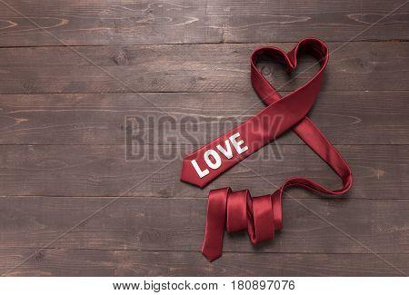 Red Heart Necktie Is On Wooden Background