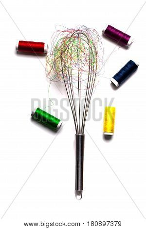 metallic beater silver cooking tool with colorful thread bobbin in web isolated on white background homemade and household concept