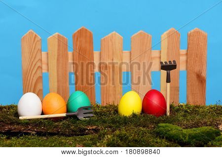 Painted Easter Colorful Eggs At Wooden Fence On Green Moss