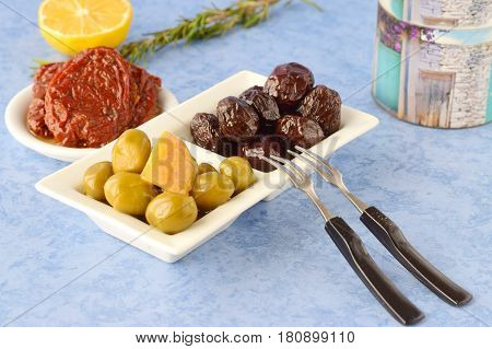 A set of dishes of greek cuisine: olives, sun dried tomatoes, lemon, beetroot, jar with olive oil and traditional dry bread. Traditional Greek food. Mediterranean lifestyle.