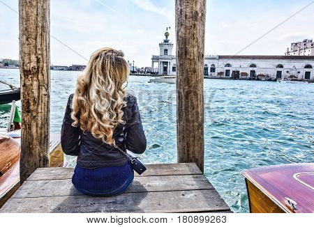 Blonde curled girl sitting on the pier in Venice. Back view
