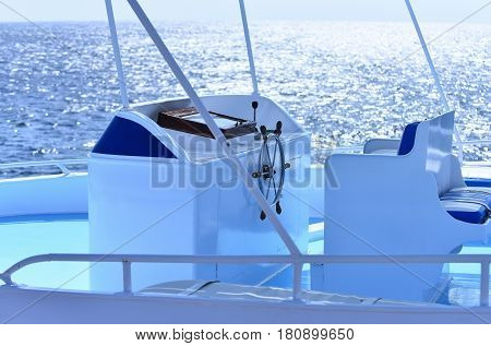 White sailing boat or yacht with steering wheel on steering stand in blue sea or ocean water on sunny day on seascape background. Idyllic summer vacation. Transport and traveling