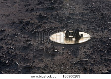Mobile photography workshop journalism. Black digital camera with professional lens on golden reflector disk on ground or soil of sand and rocky stones desert surface outdoors on grey sandy background