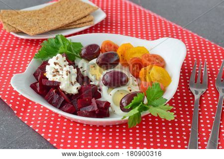 Healthy easy to cook breakfast with boiled egg, beetroot fresh tomatoes, olives, cottage cheese and flax seeds with crisps. Healthy food concept
