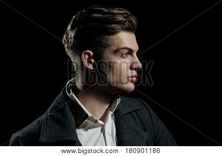 Handsome man or young caucasian unshaven macho fashion model with stylish blond hair haircut posing with serious face on black background