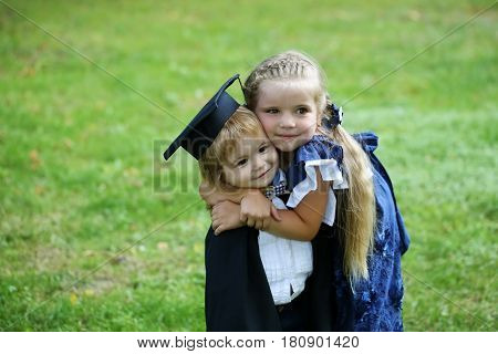 Cute little girl with long hair in blue dress hugging happy small boy in black graduation hat or cap and robe on summer day outdoors on green grass background