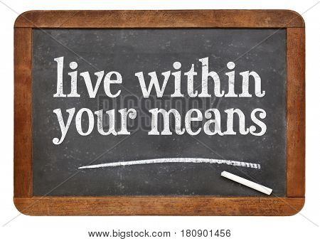 Live within your means - white chalk text on a vintage slate blackboard