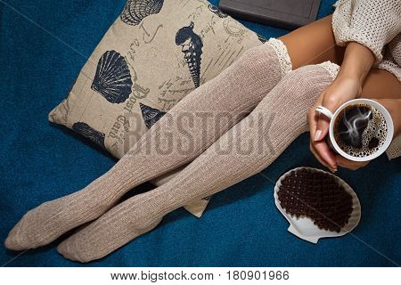 Unrecognizable teenage girl sitting on the bed with a cup of coffee and belgian waffles - horizontal top view