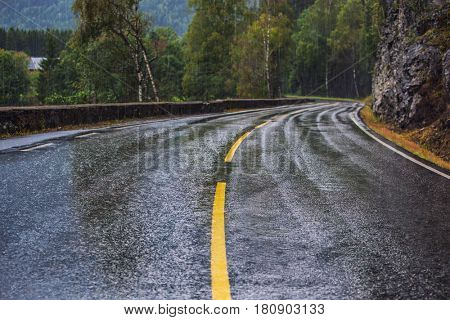 Wet road with turns at rain in Norway. Car driving safety concept.