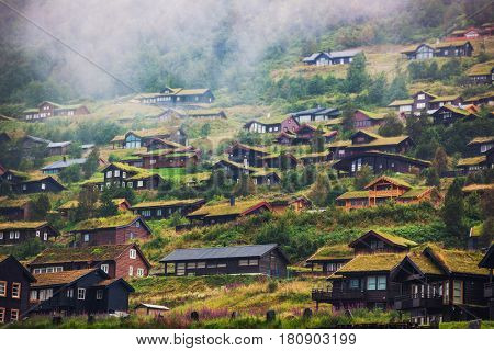Buildings on high mountains in Norway. Overcast weather with fog.
