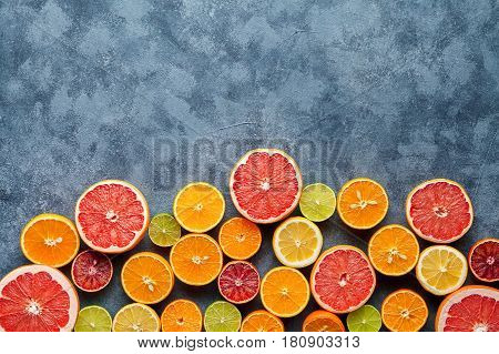 Citrus fruits sliced mix flat lay on blue concrete background, healthy vegetarian organic food, antioxidant detox diet. Tropical summer mix grapefruit, orange, apple, mandarin, kiwi fruit, lime