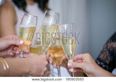 Close up of champagne glasses being chimed together during a toast by a bride and her bridesmaids.