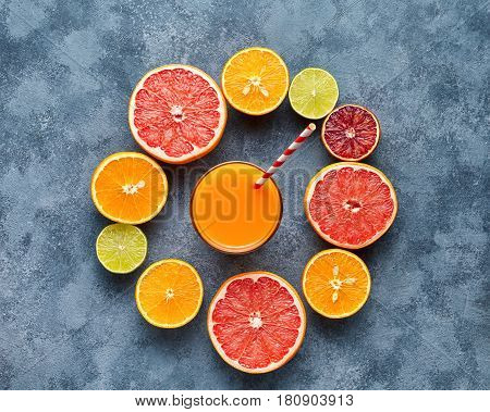 Fresh juice or smoothie vitamin c drink in citrus fruits background flat lay on concrete table, healthy lifestyle natural organic detox diet beverage. Tropical summer grapefruit, orange, apple mix
