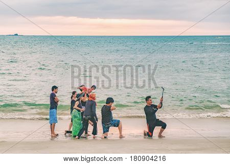 Langkawi, Malaysia - February 13, 2016:A group of young Malaysian people friends make selfies on the evening Pantai Tengah Beach Malaysia Langkawi Island. Summer vacation and fun.
