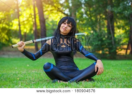 Young girl sitting on the grass and holding samurai sword. Original cosplay character