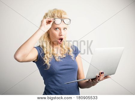 Woman in disbelief lifting up her glasses and holding laptop