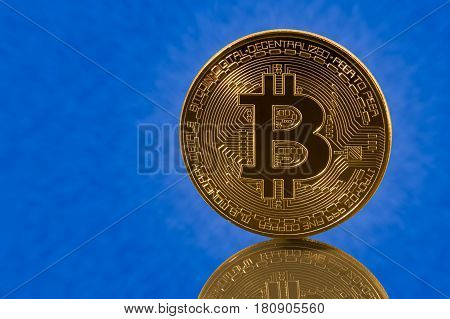 Single bit coin or bitcoin with reflection on blue cloud background to illustrate blockchain and cyber currency