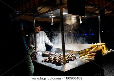 ISTANBUL, TURKEY - 11 DECEMBER 2015: Street food seller in Sultan Ahmet area preparing roasted chestnuts and corn. Traditional food carts are very famous and delicious alternative in Istanbul.
