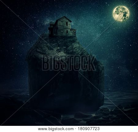 Surreal image with a wood house on the top of a rock hill near the sea beyond the starry night sky and a young man holding a rope try to catch and pull the full moon.