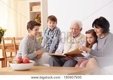 Grandparents Showing Photo Album To Grandchildren