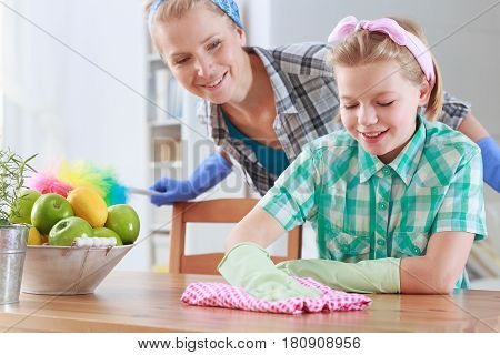 Girl Wiping A Table And Her Mum Watching Her