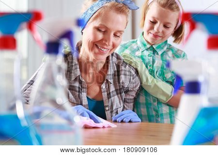 Girl Watching Her Mother Cleaning The Table