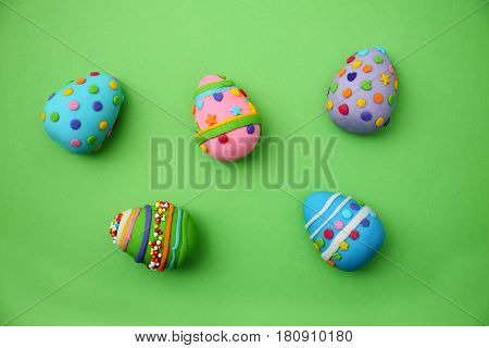 Easter cakes, eggs made of mastic on a green background