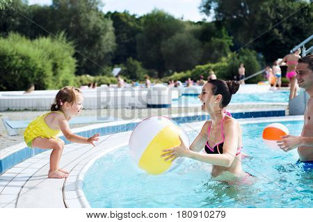 Young mother and father with their daughter in swimming pool in aqua park playing with beach ball. Summer heat and water.