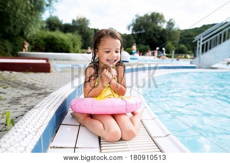 Cute little girl in swimsuit and inflatable ring lying sitting by the swimming pool. Summer heat and water.
