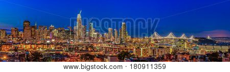 San Francisco, California, USA - April 8, 2017: San Francisco city skyline panorama at dusk with city lights the Bay Bridge and highway trail lights leading into the city