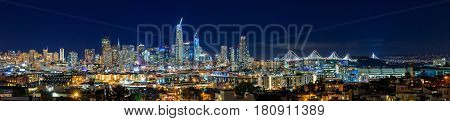 San Francisco, California, USA - April 8, 2017: San Francisco city skyline panorama after sunset with city lights the Bay Bridge and highway trail lights leading into the city