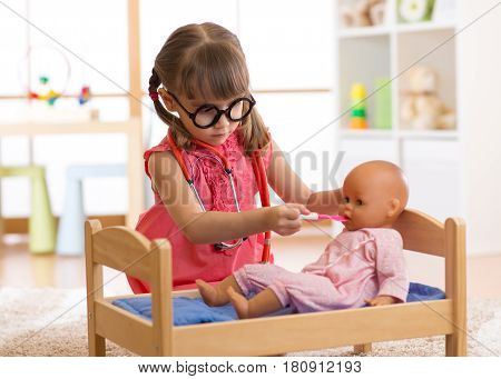 child playing doctor with doll at home