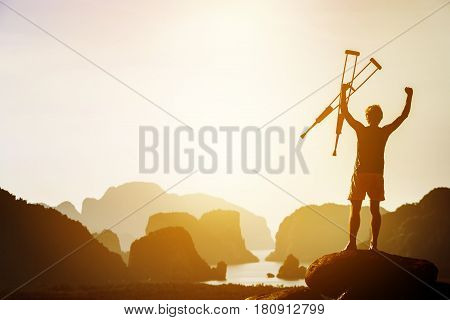 Man with crutches stands in winner pose with rised hands on mountains and islands background. Space for text