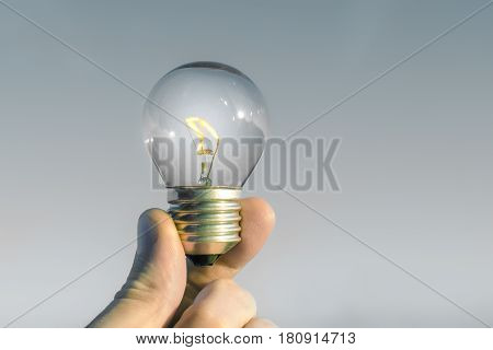 Concept idea of a burning incandescent lamp in a hand against a grey background from solar energy power