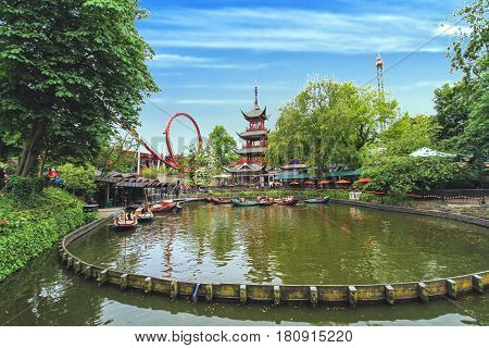 COPENHAGEN DENMARK - JUNE 15: View of Tivoli Gardens with Chinese pagoda Dragon Boat lake and Daemonen roller coaster in 2012