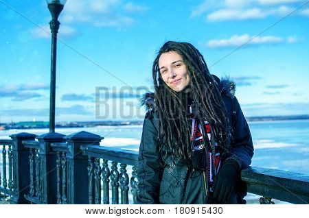 Joyful girl with dreadlocks in the snow shows her tongue in winter in the icy valley